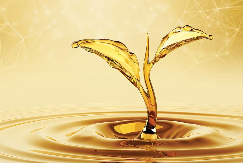 Vegetable oil drop splashing into a pool of vegetable oil