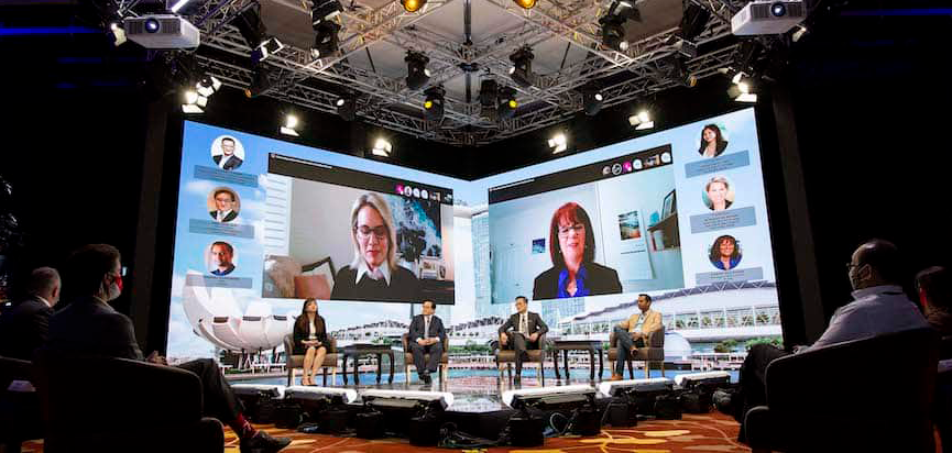 Four speakers on stage at a hybrid event with users on a livestream on a screen behind the stage